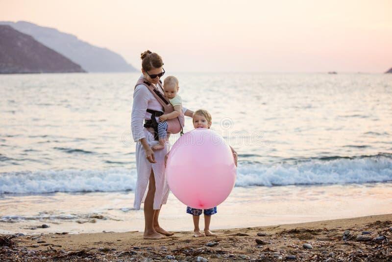 Junge kaukasische Frau mit Babytochter iand Sohn, der mit enormem rosa Ballon auf Strand spielt lizenzfreie stockbilder
