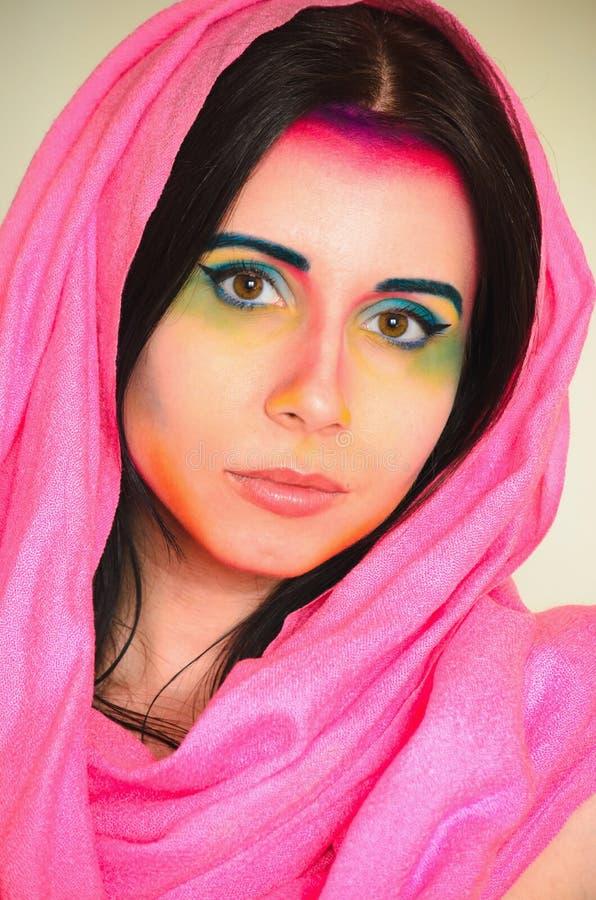 Junge kaukasische Frau mit buntem Make-up und rosa Hauptschal stockfoto