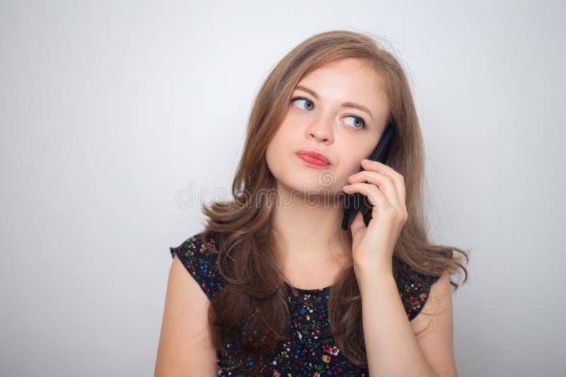Junge kaukasische Frau mit Handy schaut gestört, gereizt oder schwermütig lizenzfreie stockfotografie