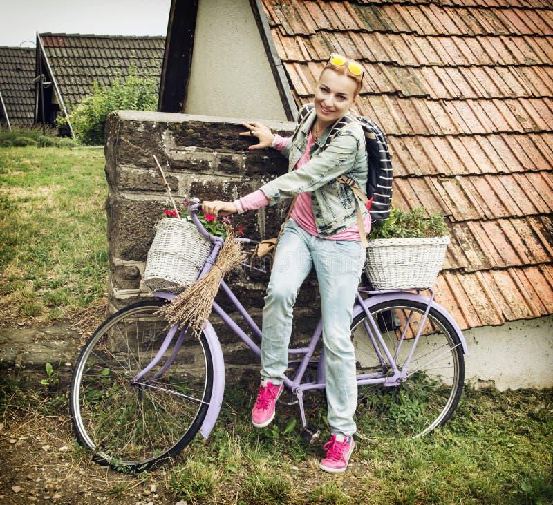 Junge kaukasische Frau sitzt auf dem violetten Fahrrad mit Docht stockbild