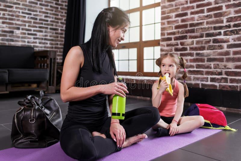 Junge kaukasische Frau und glückliches ein Mädchenkind, das nach dem Yogatraining sitzt auf Matte mit den Beinen sich entspannt,  stockfoto