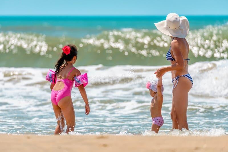 Junge kaukasische Frau und zwei kleine Töchter betrachten die kommende Welle, die Spaß durch Wasser auf sonnigem Strand Schwarzen stockfoto