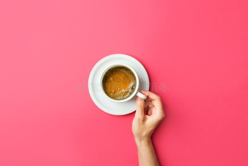 Junge kaukasische Frauenhände hält weiße Schale mit frisch gebrautem Kaffee mit schäumendem crema auf Untertasse auf pinkfarbenem stockbilder