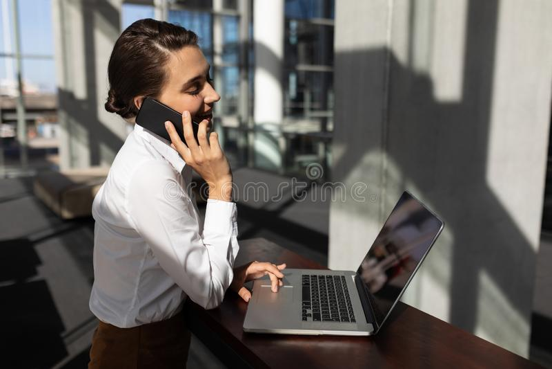 Junge kaukasische Geschäftsfrau, die am Handy während unter Verwendung des Laptops im modernen Büro spricht stockbilder