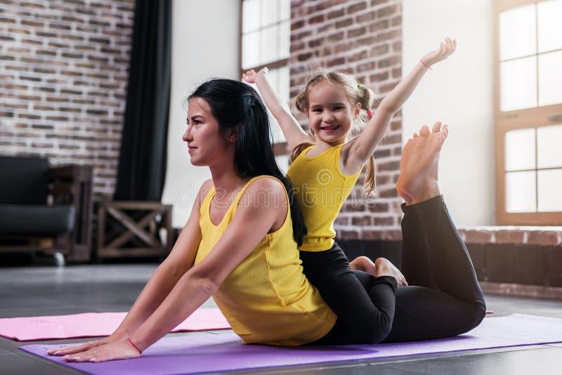 Junge kaukasische Mutter, die Yogakobrahaltung auf Boden während ihre lächelnde Tochter zurück sitzt auf Müttern tut stockbilder