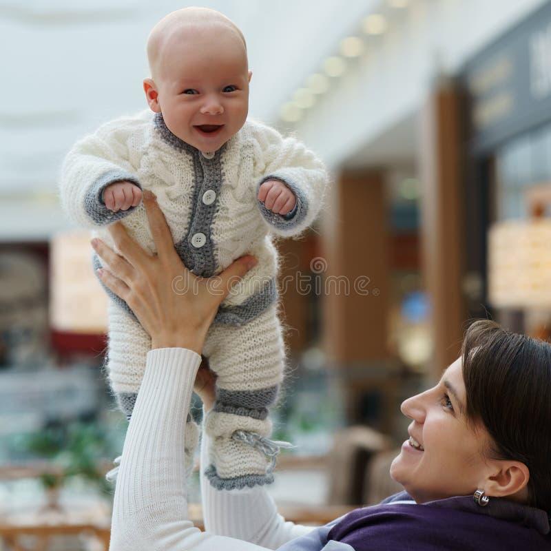 Junge kaukasische Mutter spielt mit ihrem netten lustigen Säuglingssohn, throing ihn hoch und fängt wieder am öffentlichen Ort stockfoto