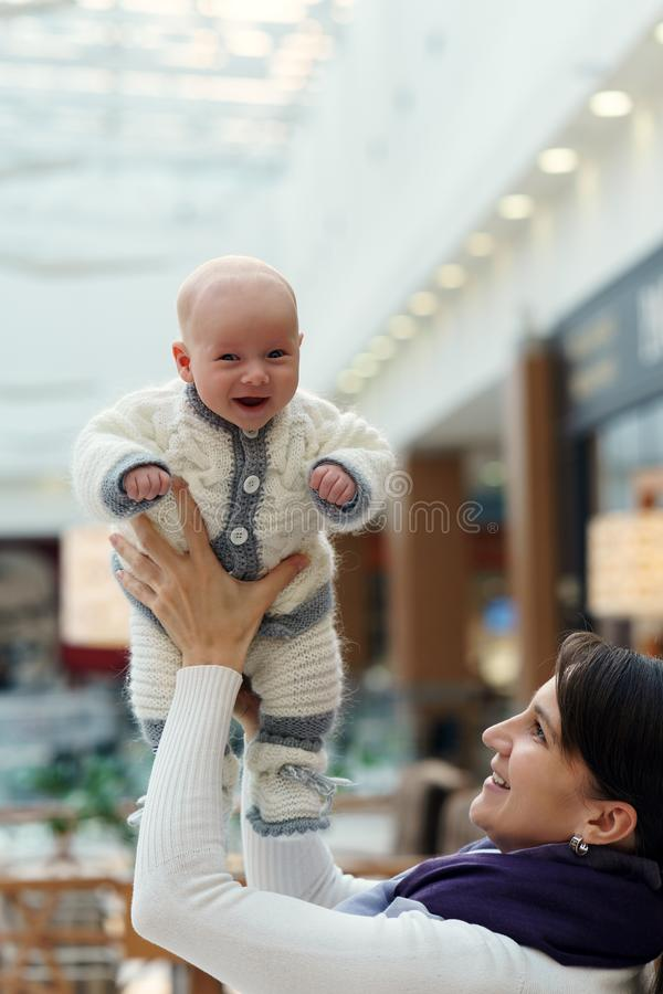Junge kaukasische Mutter spielt mit ihrem netten lustigen Säuglingssohn, wirft ihn hoch und fängt wieder am öffentlichen Ort stockfotografie