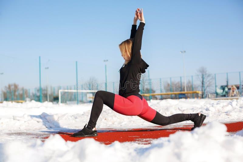 Junge kaukasische weibliche Blondine in den roten Gamaschen, die Übung auf einer roten Laufbahn in einem schneebedeckten Stadion  stockfoto