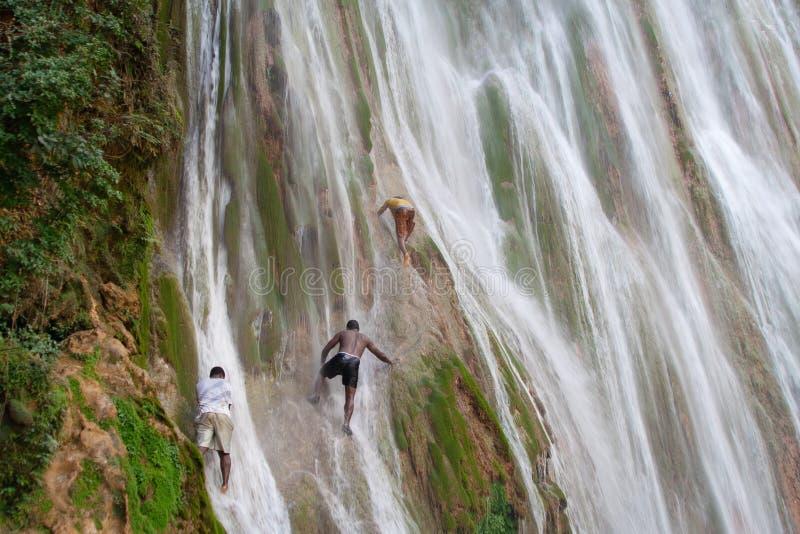 Junge Kerle klettern die Leisten einer Klippe auf dem Wasserfall stockfotos