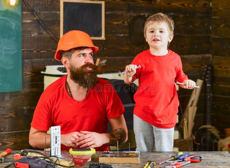 Junge, Kindernette Griffbolzen oder Schrauben, Spaß beim handcrafting habend mit Vati Getrennt über weißem Hintergrund Vater, Elt lizenzfreies stockfoto