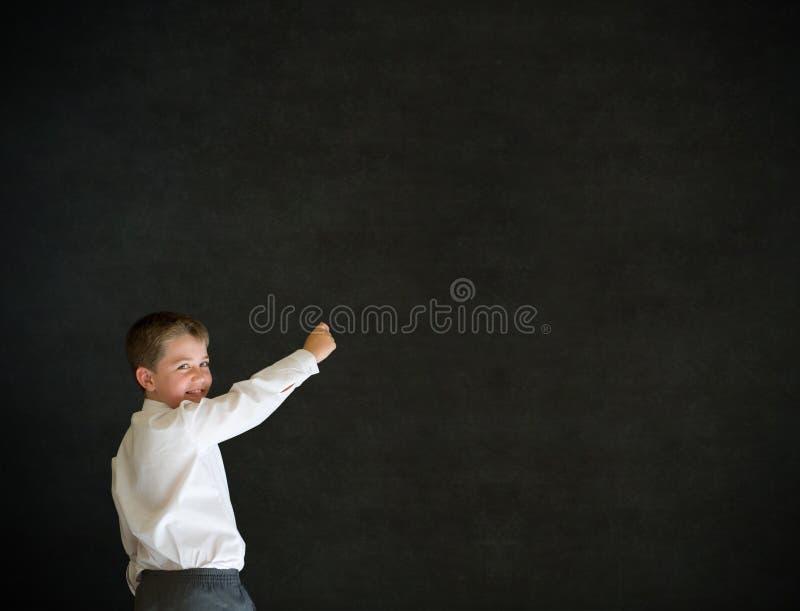 Junge kleidete oben als Geschäftsmannschreiben auf Tafel an stockfotos