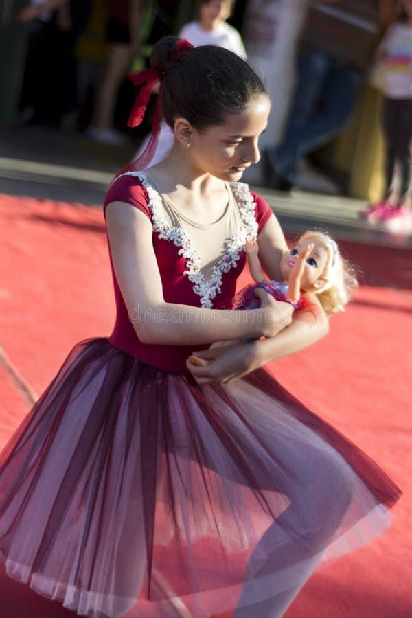 Junge kleine Ballerina mit Puppe in den Armen auf allgemeiner Tanzbühne lizenzfreie stockfotos