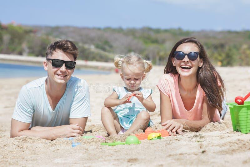 Junge kleine Familie, die Spaß zusammen auf dem Strand hat lizenzfreie stockfotografie