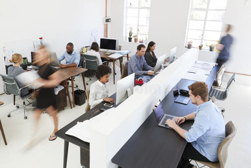 Junge Kollegen an den Computern in einem beschäftigten Bürogroßraum stockfoto