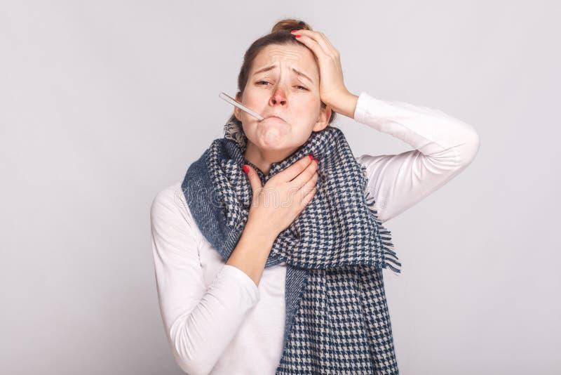 Junge kranke Frau, die Kehle und Kopf hält Haben Sie eine Temperatur stockfotos