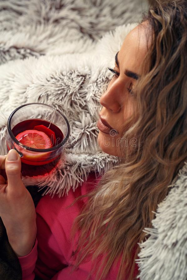 Junge kranke Frau im Bett, trinkender Kräutertee Vitamine und heißes lizenzfreie stockbilder