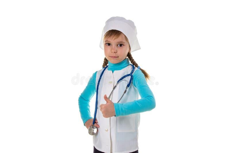 Junge Krankenschwester, die oben den Stethoskopdaumen mit den Fingern, ausgezeichnetes Zeichen trägt lizenzfreie stockfotos