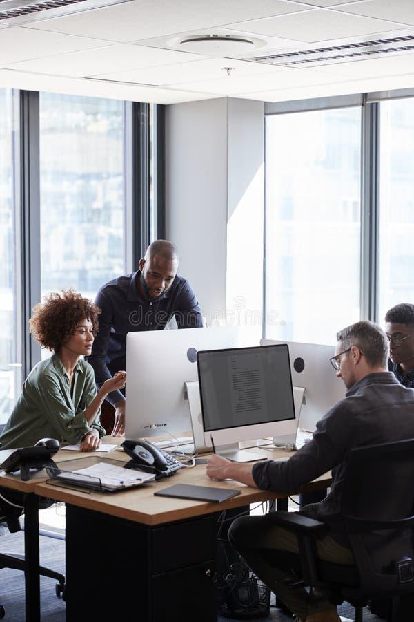 Junge kreative Fachleute, die an den Computern in einem zufälligen Büro, vertikal zusammenarbeiten lizenzfreies stockbild
