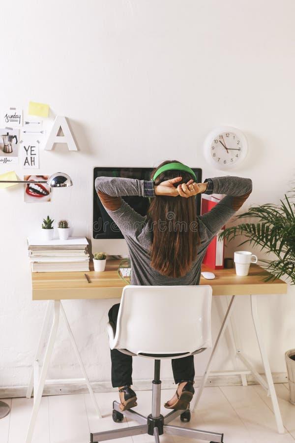 Junge kreative Frau, die im Büro sich entspannt lizenzfreie stockfotografie