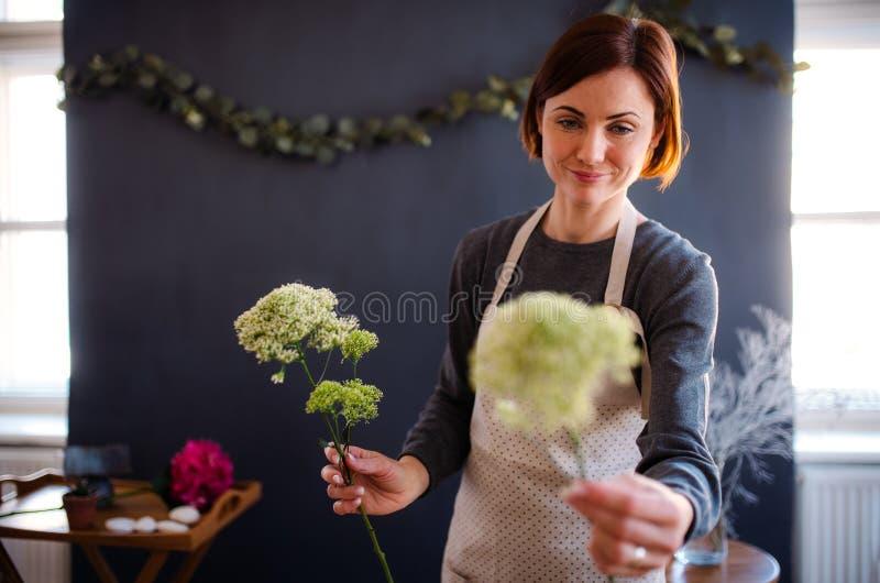 Junge kreative Frau in einem Blumenladen Ein Start des Floristengesch?fts stockbild