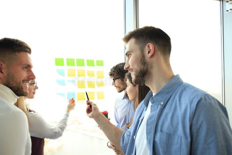 Junge kreative Startgeschäftsleute auf dem Treffen im modernen Büro, das Planprojekte mit Postenaufklebern auf Glas macht stockfotografie