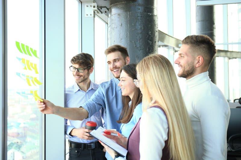 Junge kreative Startgesch?ftsleute auf dem Treffen im modernen B?ro, das Planprojekte mit Postenaufklebern auf Glas macht lizenzfreies stockbild
