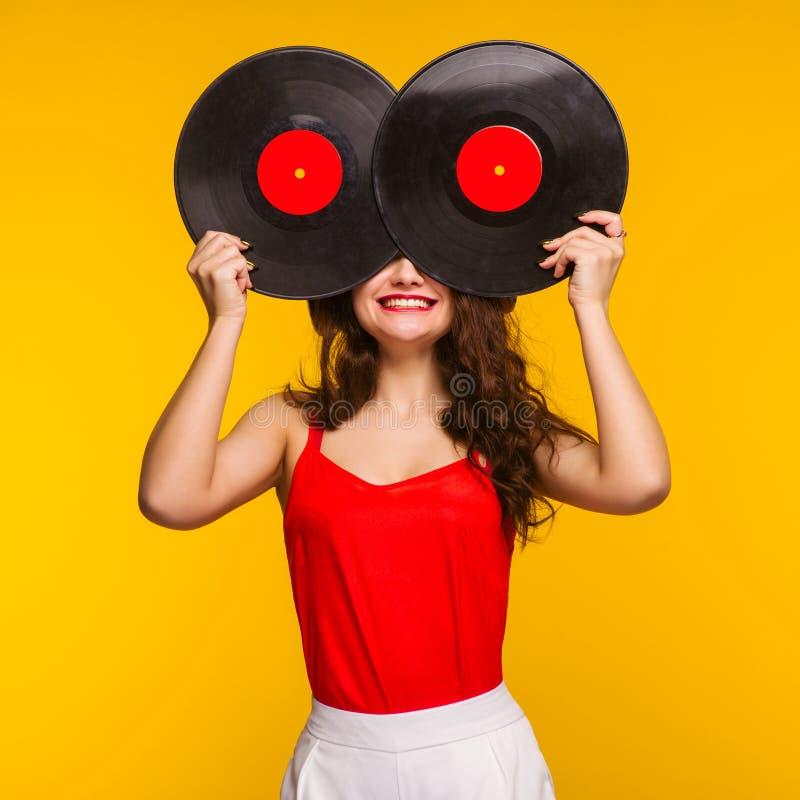 Junge lächelnde Frau, die ihr Gesicht mit Vinylaufzeichnungsdisketten schließt stockfoto