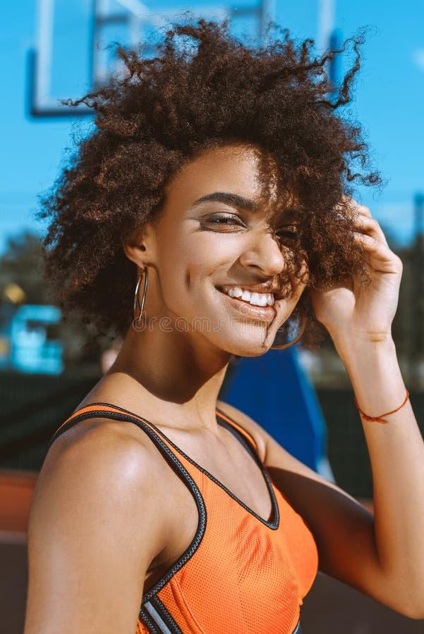 junge lächelnde Afroamerikanerfrau im hellen Sport-BH, der mit ihrer Hand in ihr aufwirft stockfotos