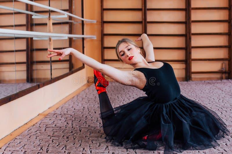 Junge lächelnde Ballerina, die Übung in der Trainingshalle tut stockfotografie
