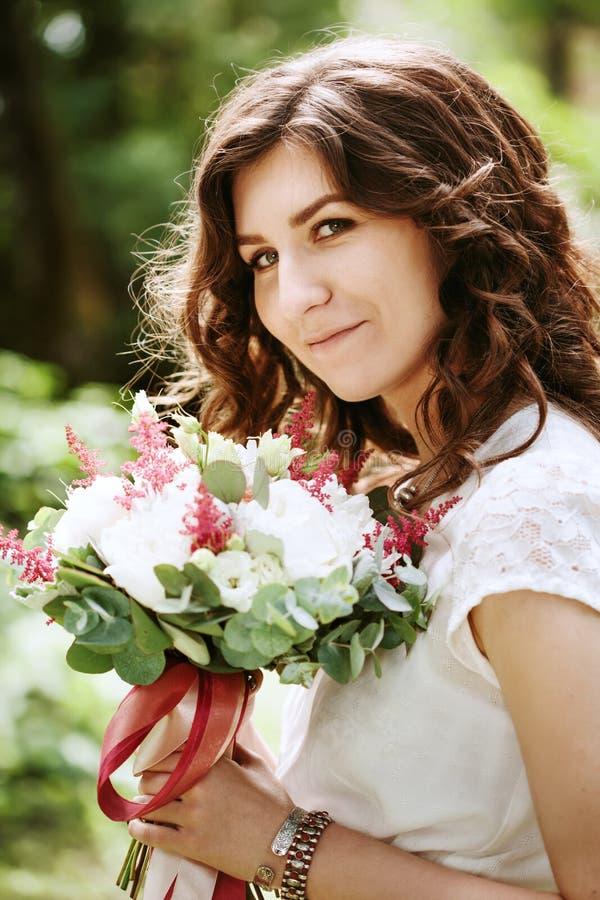 Junge lächelnde Braut mit Hochzeitsblumen stockfotos
