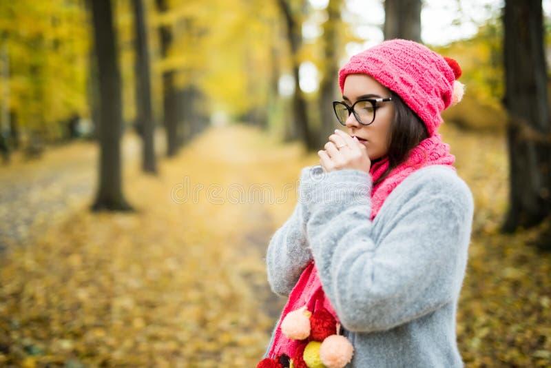 Junge lächelnde Brunettefrau, die gestrickte Strickjacke, Handschuhe, Schal und Hut trägt stockfotografie
