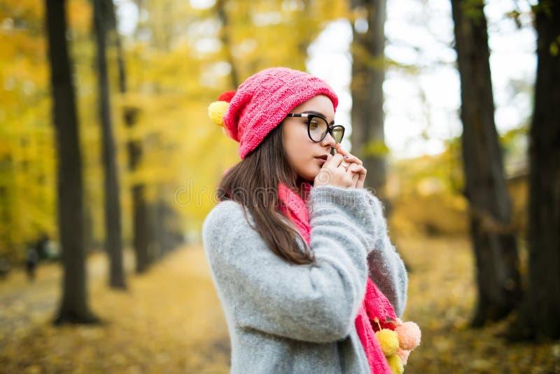 Junge lächelnde Brunettefrau, die gestrickte Strickjacke, Handschuhe, Schal und Hut trägt stockfoto