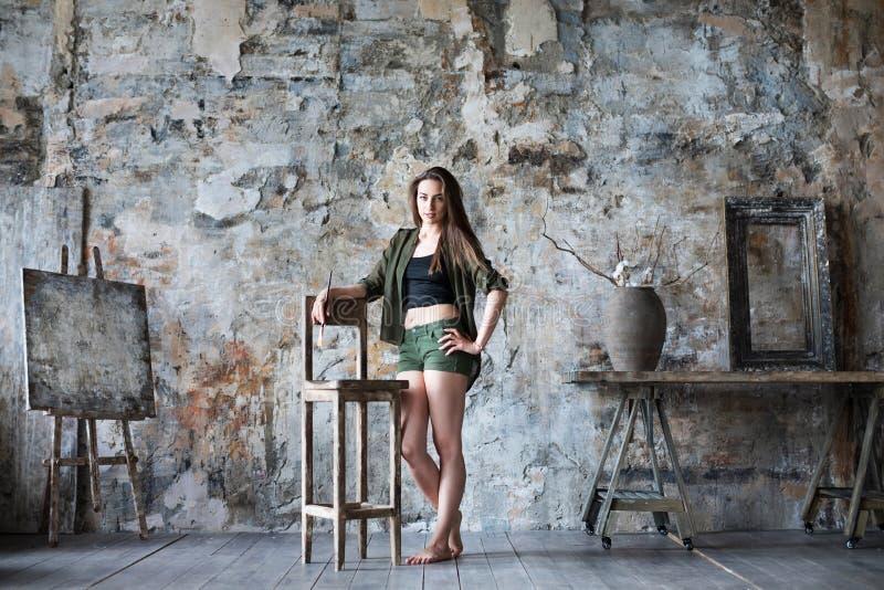 Junge lächelnde Brunettekünstlerin in ihrem Studio hält eine Bürste stockbilder
