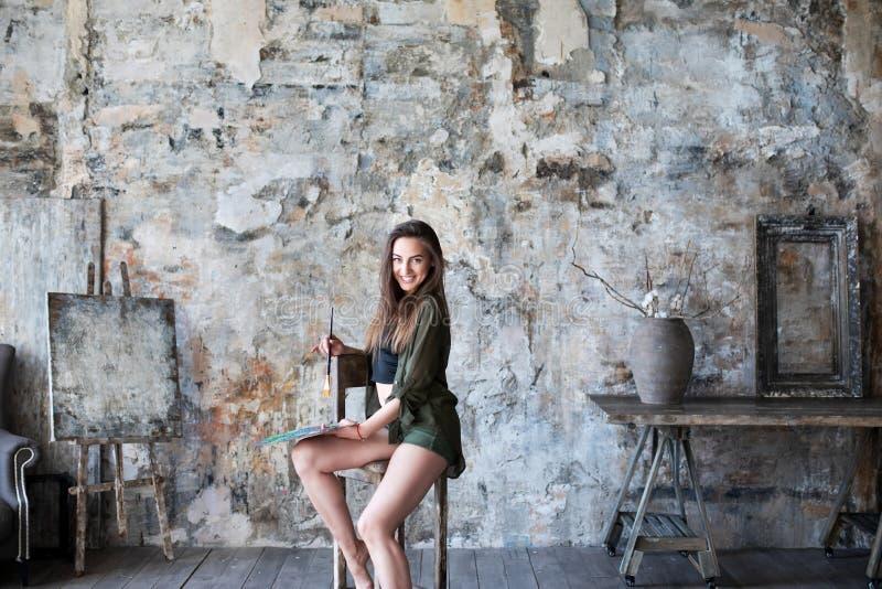 Junge lächelnde Brunettekünstlerin in ihrem Studio hält eine Bürste stockfotos