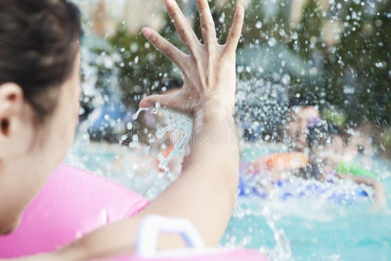 Junge lächelnde Familie, die im Pool spritzt und spielt stockfoto