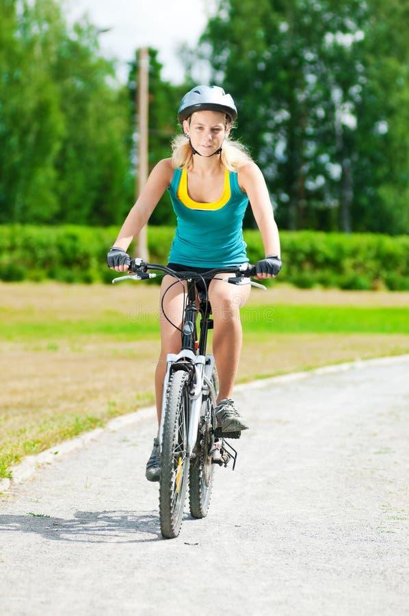 Junge lächelnde Frau auf Fahrrad stockfotografie