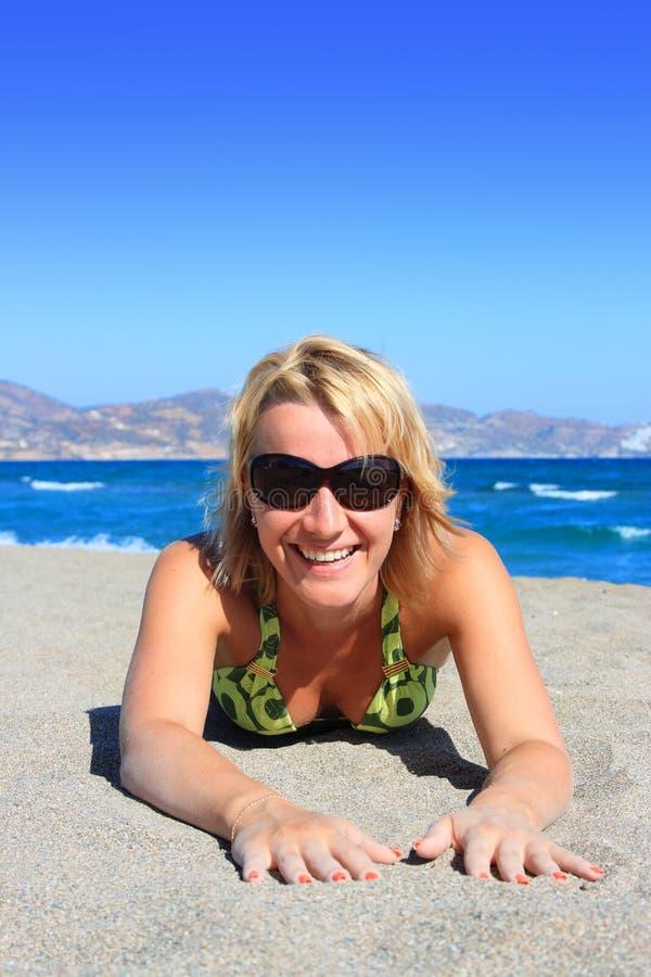 Junge lächelnde Frau auf Seeküste lizenzfreie stockbilder