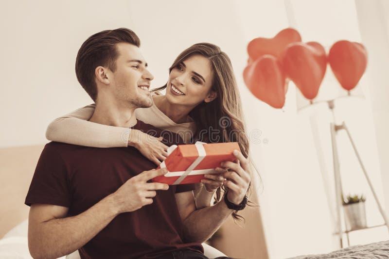 Junge lächelnde Frau beim Bewundern ihres hübschen eleganten Mannes stockbild