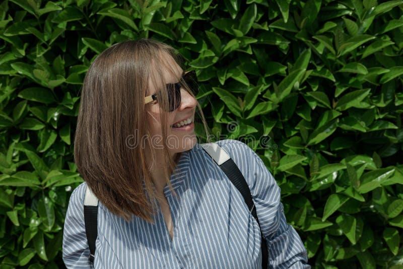 Junge lächelnde Frau in der Sonnenbrille mit einem Rucksack auf einem Grün national stockfotografie