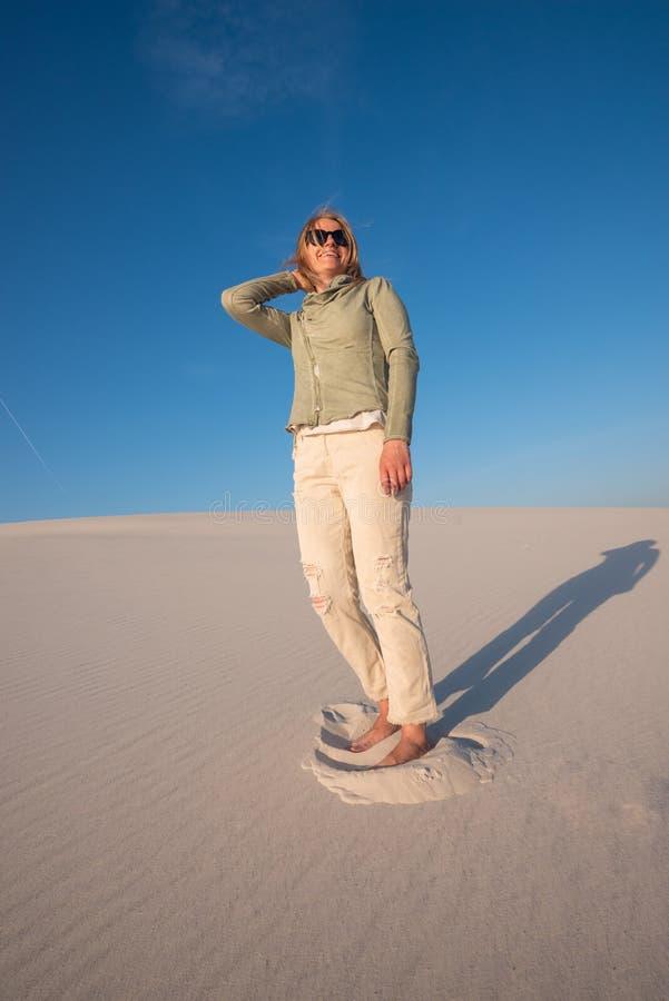 Junge lächelnde Frau in der Sonnenbrille steht auf dem Strand lizenzfreies stockfoto