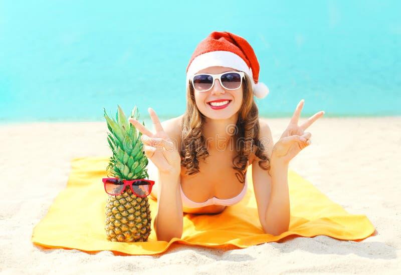 Junge lächelnde Frau des Weihnachtsporträts recht in rotem Sankt-Hut und -ananas, die auf Strand über Meer liegt lizenzfreie stockbilder