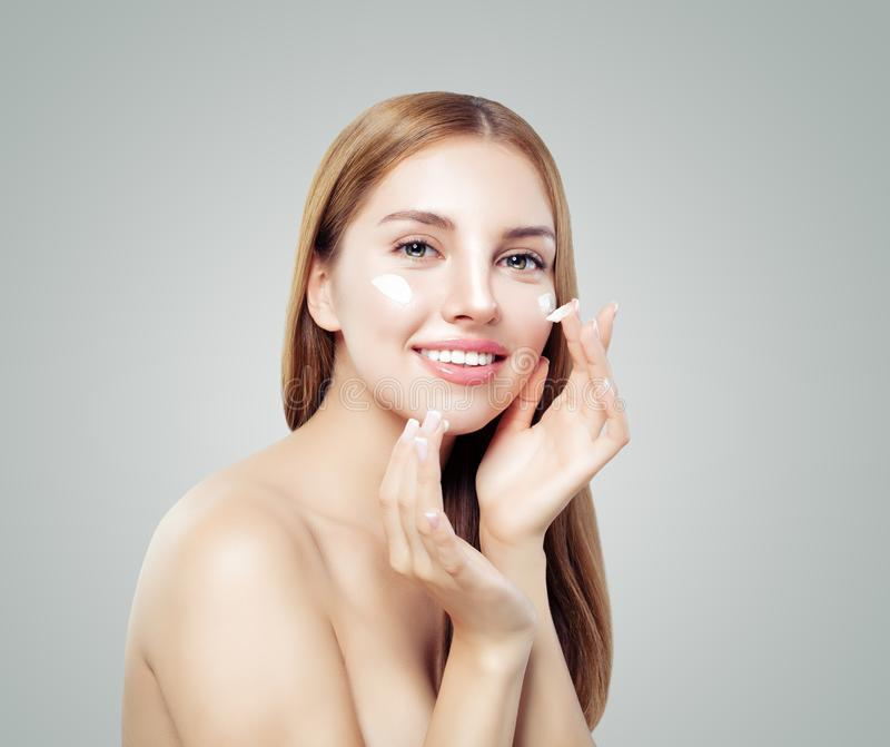 Junge lächelnde Frau, die Creme auf ihrer gesunden Haut aufträgt Weibliches Gesicht Gesichtsbehandlungs- und Hautpflegekonzept lizenzfreies stockfoto