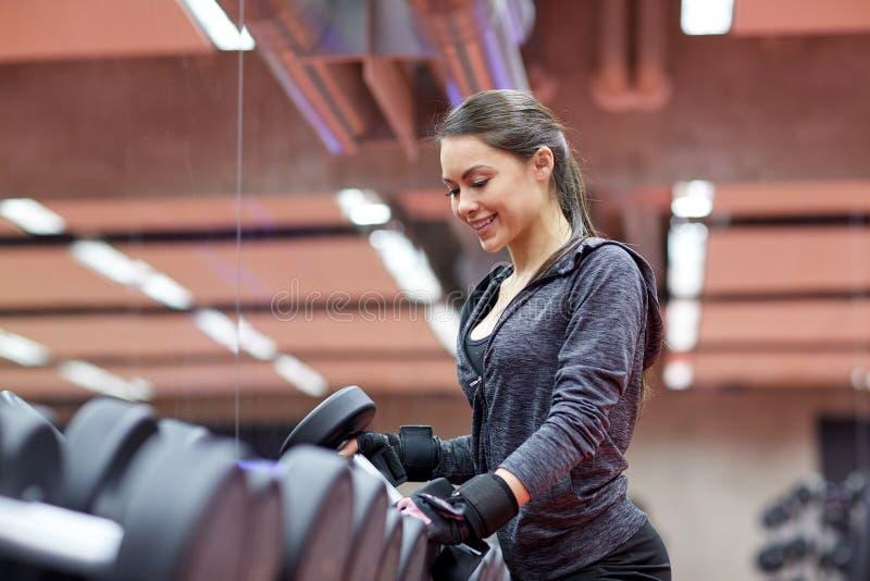 Junge lächelnde Frau, die Dummköpfe in der Turnhalle wählt lizenzfreie stockfotos