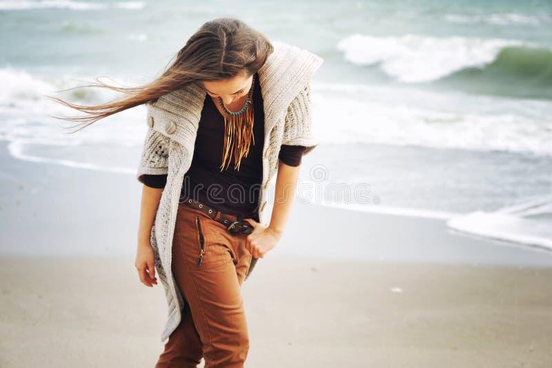 Junge lächelnde Frau, die durch einen Seestrand, Herbstmode, gesundes Lebensstilkonzept geht lizenzfreie stockbilder