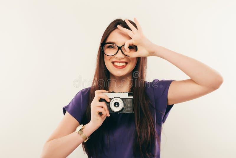 Junge lächelnde Frau, die ein Foto durch alte Fotokamera macht photograph stockfoto