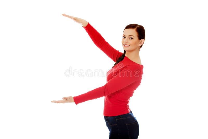 Junge lächelnde Frau, die etwas darstellt lizenzfreie stockbilder