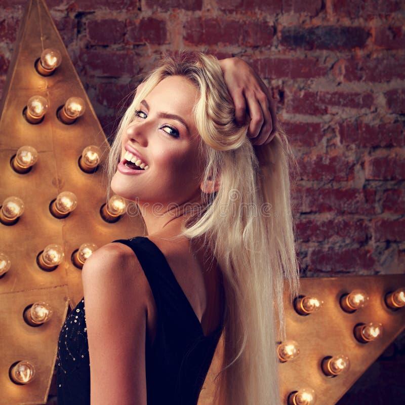 Junge lächelnde Frau, die die Hand halten das lange blonde Haar auf Stern- und Backsteinmauerhintergrund aufwirft Getonte Nahaufn lizenzfreies stockfoto