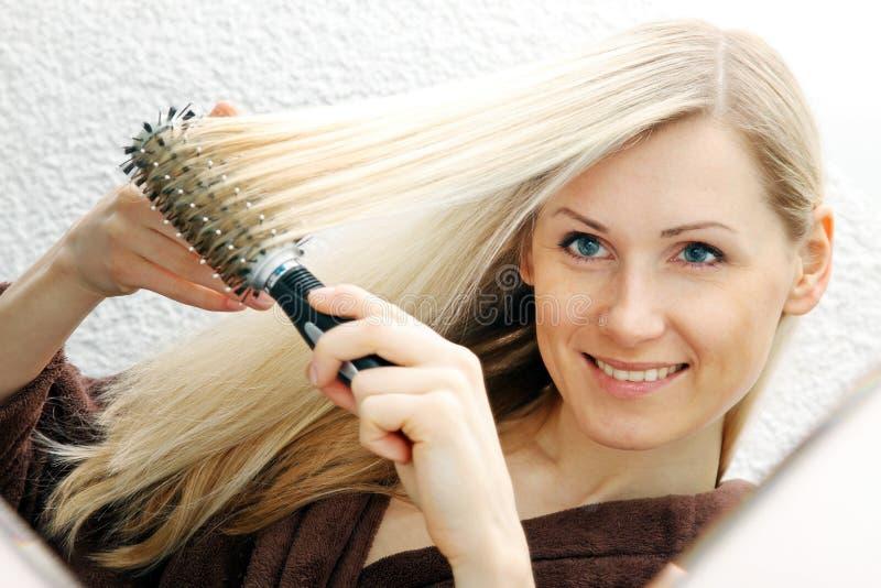 Junge lächelnde Frau, die ihr langes blondes Haar bürstet stockbild