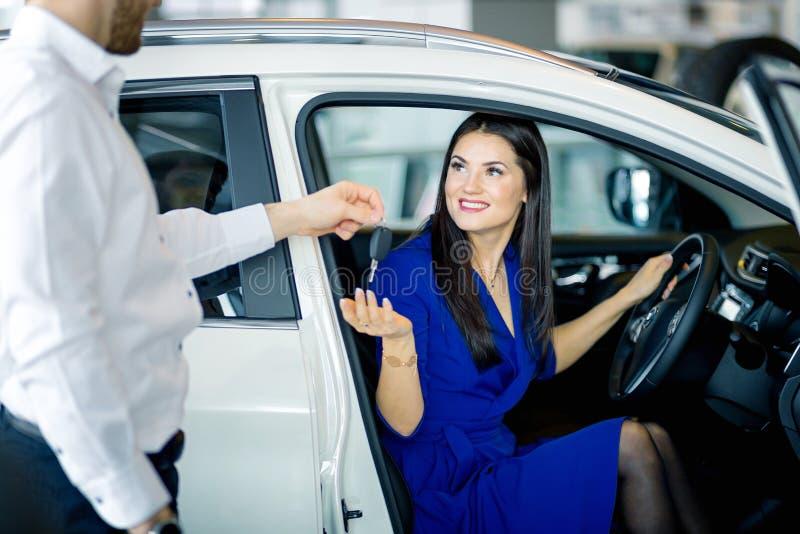 Junge lächelnde Frau, die im Auto empfängt Schlüssel sitzt Miete, Kauf, verkaufend stockbilder