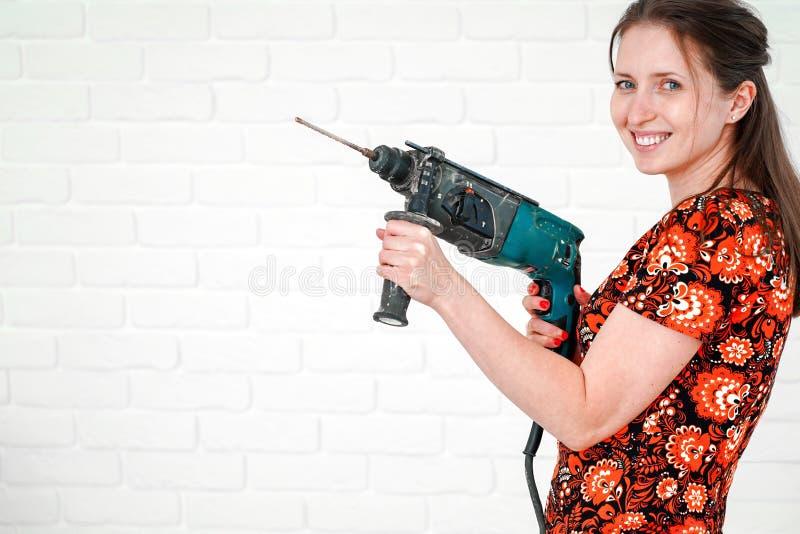 Junge lächelnde Frau, die mit Hammer aufwirft lizenzfreie stockbilder